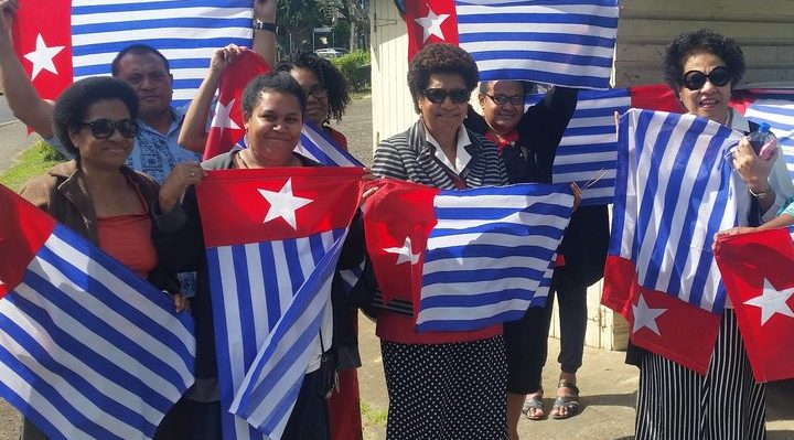 Ro Teimumu Kepa (centre) with staff flying the West Papua flag. Photo: supplied